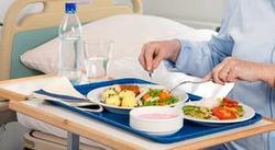 Tablett mit verschiedenen Speisen und einer Flasche Wasser am Bett serviert